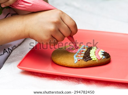 Child decorating shortbread cookies with icing from piping bag - stock photo