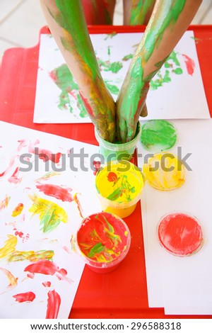 Child dipping fingers in washable, non-toxic finger paints, painting a drawing. Sensory play, innovative approach to learning, fun childhood concept. - stock photo