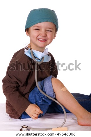 Child doctor putting a bandage on his knee. - stock photo