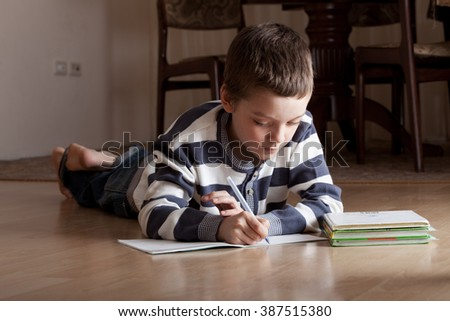 Child does lessons lying on the floor - stock photo