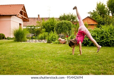 Child doing cartwheel in backyard - stock photo
