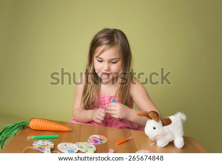 Child doing Easter activities and crafts with bunny stickers, Easter Egg shapes, pencils and markers. - stock photo