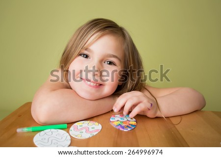 Child doing Easter activities and crafts with Easter Egg shapes, pencils and markers. - stock photo