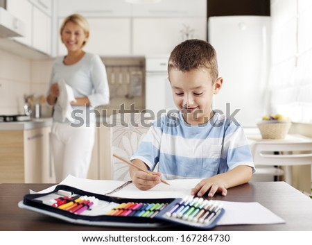 Child doing his homework with his mother working in the background