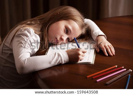 Child doing homework. Sad girl writing, reading - stock photo