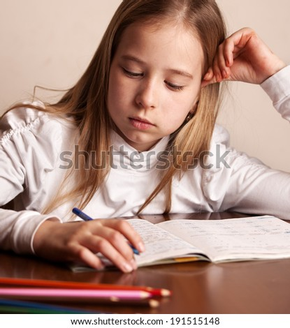 Child doing homework. Sad girl writing, reeding - stock photo