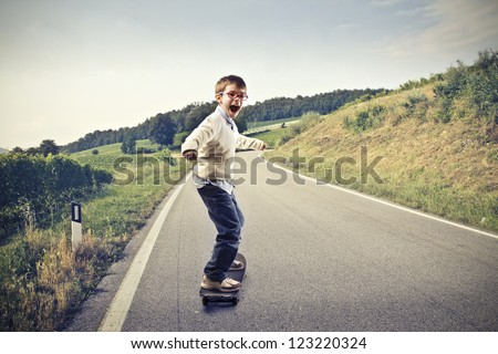 Child doing skateboard on a long road - stock photo