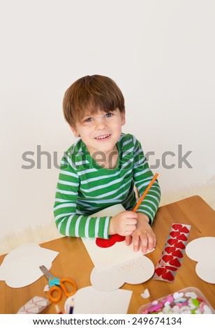 Child doing Valentine's day arts and crafts with hearts, pencils, paper - stock photo
