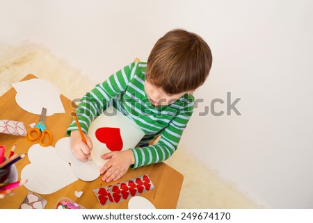 Child doing Valentine's day arts and crafts with hearts, pencils, paper