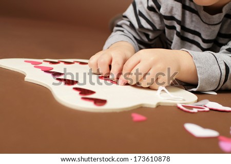Child doing Valentine's Day Craft with Heart stickers - stock photo