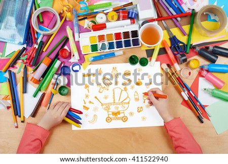 child drawing baby stuff - pram, wear and toys, top view hands with pencil painting picture on paper, artwork workplace - stock photo