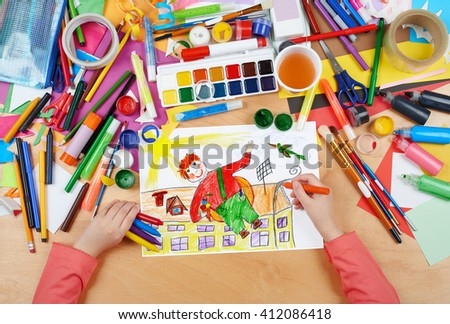 child drawing boy fly with air screw on his back, top view hands with pencil painting picture on paper, artwork workplace - stock photo