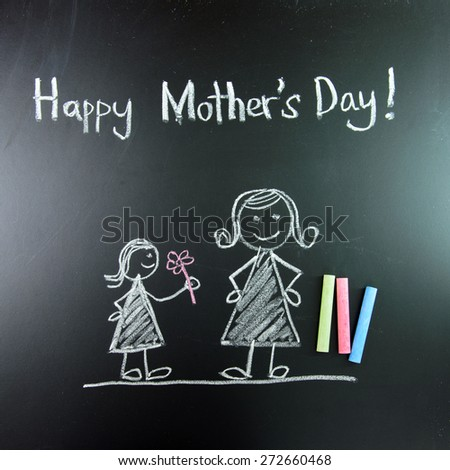 Child drawing of happy mother's day picture using chalk on blackboard - stock photo