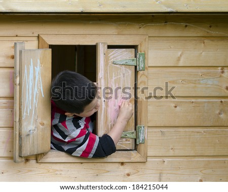Child drawing on a window shutter of a playhouse with a chalk.  - stock photo