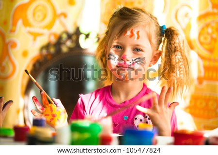 Child, drawing paint with paint of face. - stock photo