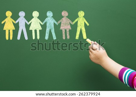 Child drawing people united on blackboard - stock photo
