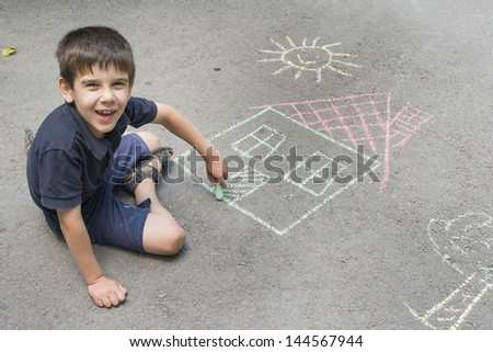 Child drawing sun and house on asphalt in a park - stock photo