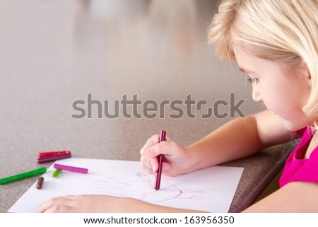 Child drawing with crayons, sitting at table in kitchen at home - stock photo