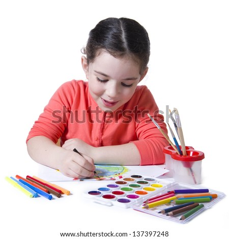 Child drawing with pensil using a lot of painting tools
