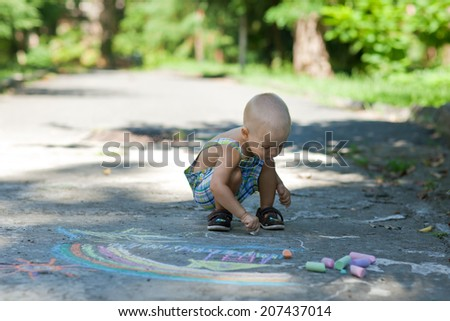 Child draws color pieces of chalk in park
