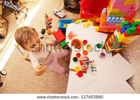 child draws in kindergarten colored watercolors. little boy playing in the room - stock photo