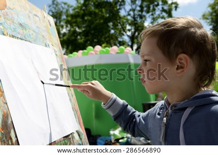 Child draws paints on the paper in the park - stock photo