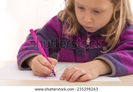 Child draws the picture with color pen. Serious, absorbed face.