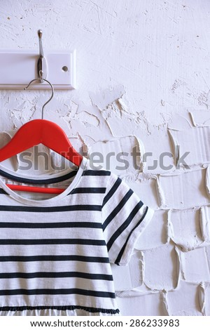 Child dress on hanger on white wall background