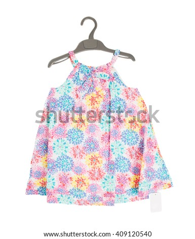 Child dress with floral pattern on black plastic hanger. Isolated on a white background. - stock photo