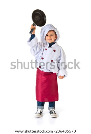 child dressed as a chef holding fried pan  - stock photo