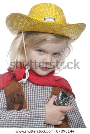 Child dressed as a cowgirl, is holding badge. She is looking directly at the camera