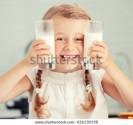 Child drinking milk at home. Happy little girl eating at home - stock photo