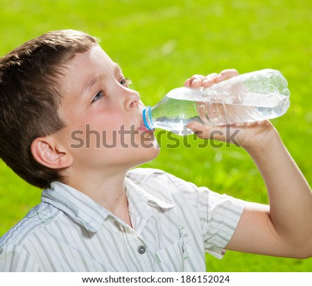 Child drinking water. Boy outdoors - stock photo