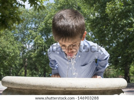 Child drinking water from a fountain. Close up - stock photo
