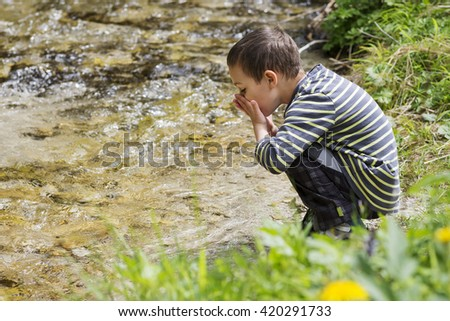 Child drinking water from clean mountain river, environmental concept.