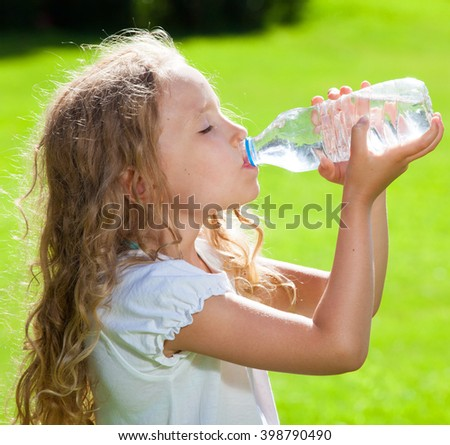 Child drinking water. Girl outdoors - stock photo