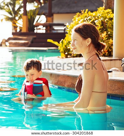Child drinking watermelon shake near mother  in the pool - stock photo
