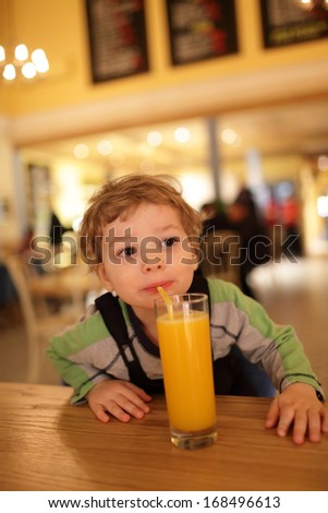 Child drinks orange juice at a cafe