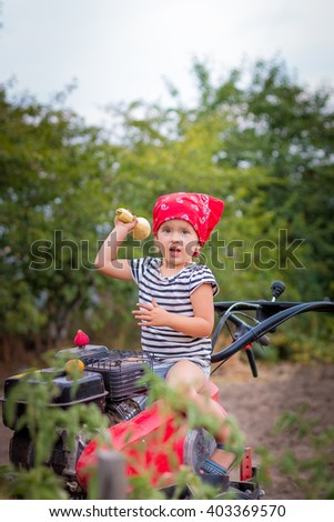 Child drives the tiller. Baby girl with squash in the hand on the red tractor in the garden.