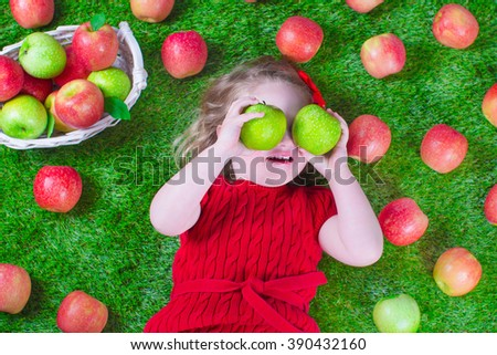 Child eating apple. Little girl playing peek a boo holding fresh ripe apples. Kids eating snack relaxing on a lawn. Children summer fun on a farm picking healthy fruit. - stock photo