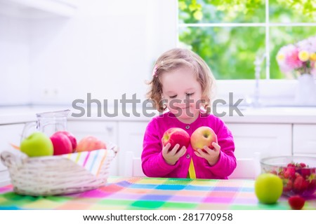 Child eating breakfast. Kids eat in a white kitchen. Children having fresh fruit. Little kid playing peek a boo with apples. Preschooler girl with apple and strawberry. Healthy nutrition for toddlers. - stock photo