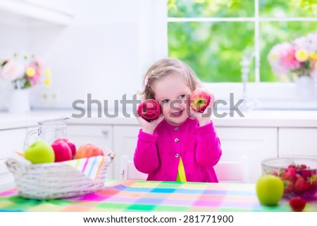 Child eating breakfast. Kids eat in a white kitchen. Children having fresh fruit. Little kid playing peek a boo with apples. Preschooler girl with apple and strawberry. Healthy nutrition for toddlers.