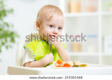 child eating healthy food with a spoon at home - stock photo
