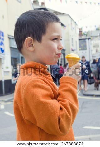 Child eating ice cream on a street in England. - stock photo