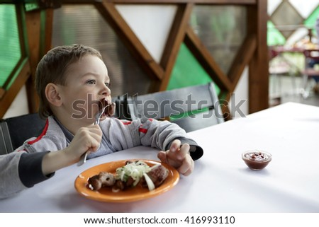 Child eating kebab with onions in the cafe