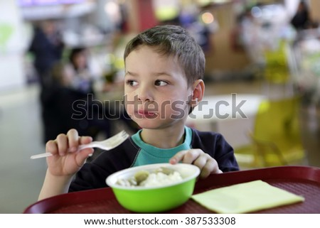 Child eating meat dumplings in the fast food area