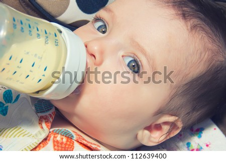 child eating out of a plastic bottle - stock photo