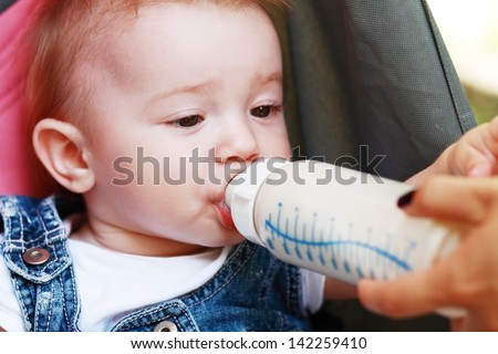 child eating out of a plastic bottle outdoor - stock photo