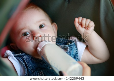 child eating out of a plastic bottle outdoor