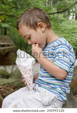 Child eating popcorn from a paper bag, while sitting on a bench in a park or garden.